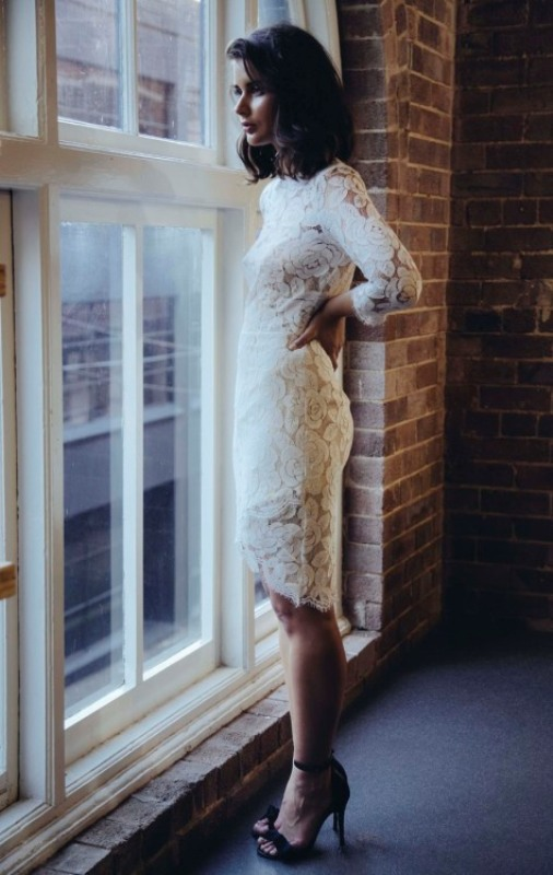 an over the knee white lace dress with long sleeves and black shoes for a minimal spring outfit