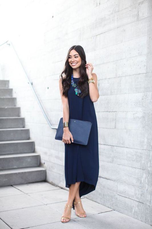 a modern navy sleeveless dress with an asymmetrical skirt, a matching clutch, silver shoes and a statement necklace