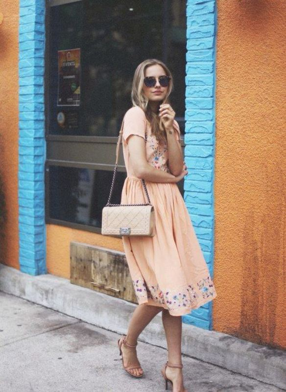a blush midi dress with floral embroidery in blue, nude shoes and a nude bag for a spring wedding