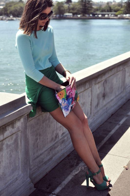 a light blue top, a green wap mini skirt, green platform shoes and a colorful floral print clutch