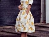 a white and yellow over the knee dress with short sleeves, black heels and a small clutch