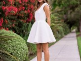 a white A-ine mini dress with no sleeves, a deep cut and red shoes for a bold and cool modern look