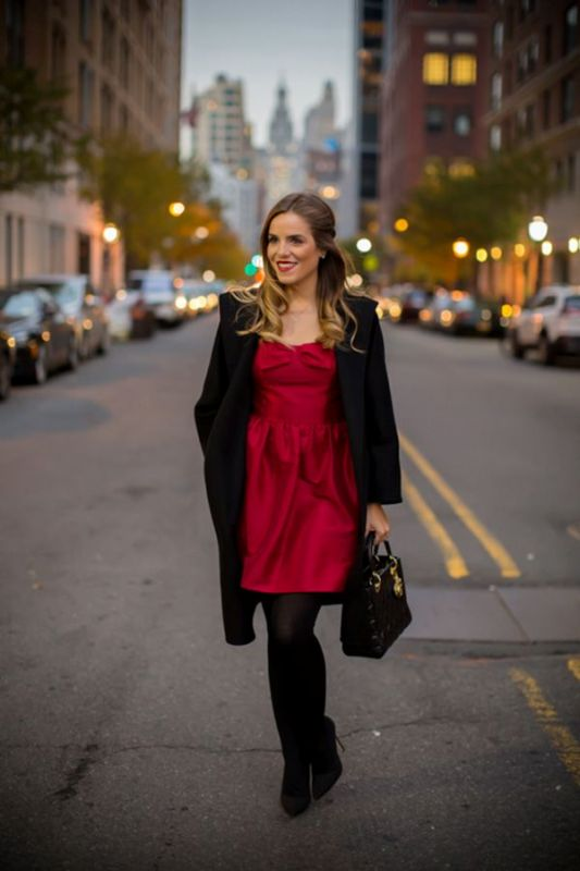 a chic burgundy mini dress, black tights, a black coat and a black bag, black shoes for a bold fall look