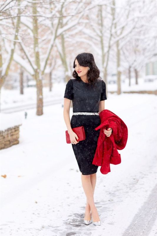 a classic black sheath knee dress with a high neckline, short sleeves, a shiny sash, silver shoes, a red clutch and a red coat