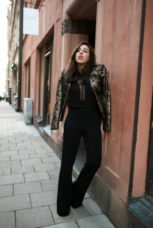 a black jumpsuit with a covered plunging neckline, a gold and black shiny cropped jacket