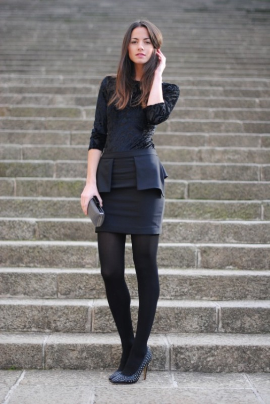 a black sheath mini dress with lace detailing and a peplum, black tights, navy embellished shoes and a metallic clutch