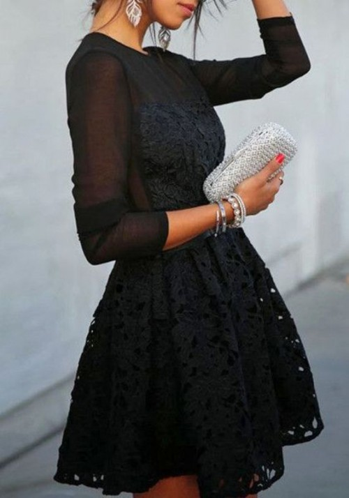 a black A-line mini dress with lace detailing, long sleeves and a high neckline, stacked bracelets and a shiny silver clutch