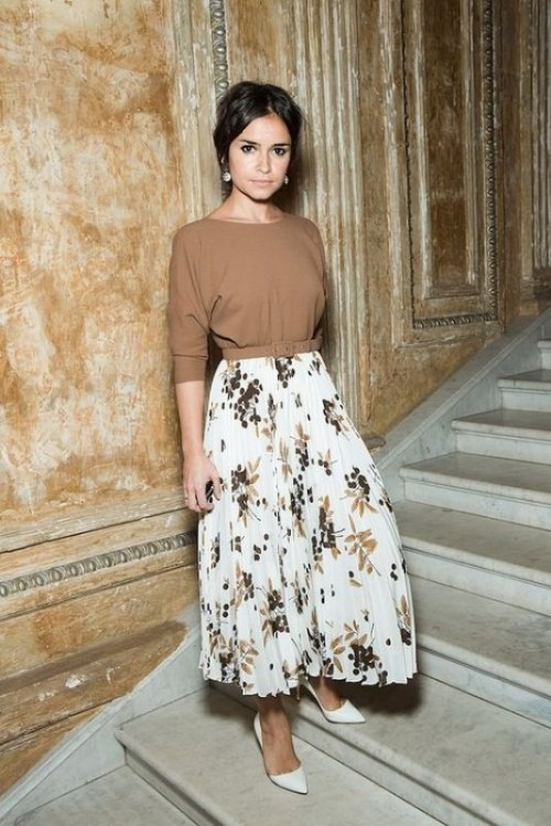 a tan long sleeve top, a floral white a-line midi skirt, white heels and statement earrings for a bold look