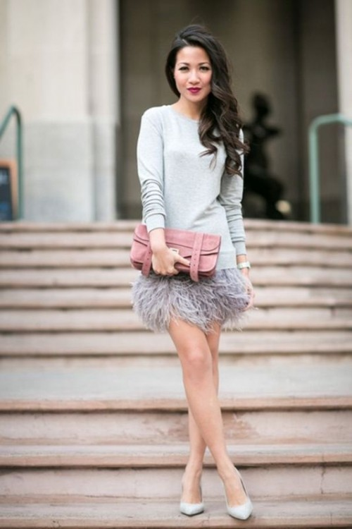 a grey oversized sweater, an ostrich feather mini skirt, grey shoes and a pink suede clutch
