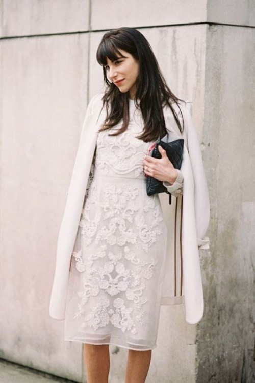 a white lace sheath knee dress, a white coat, a black leather clutch for a refined winter wedding guest look