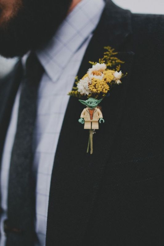 a small and fun Star Wars wedding boutonniere with white and yellow blooms and a little Yoda figurine is a fun idea to accessorize a groom's look