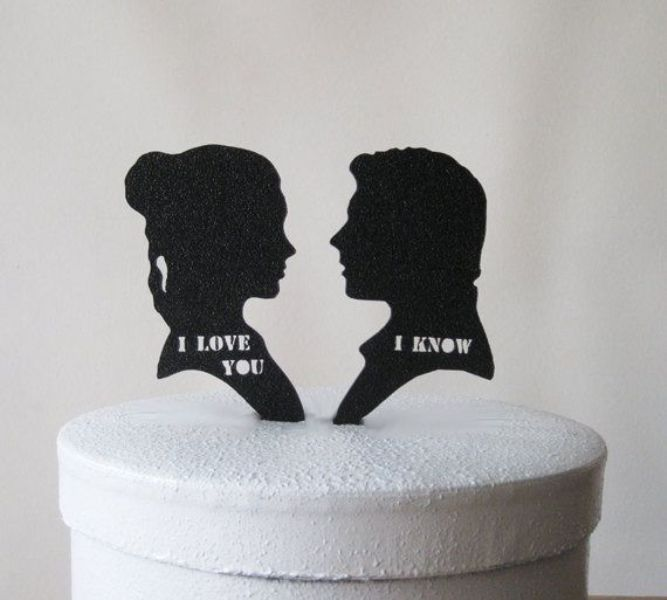 a wedding cake topped with silhouettes of Lea and Han Solo and their favorite phrases