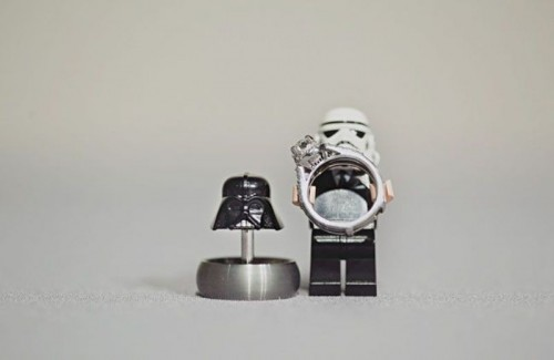 a Stormtrooper holding a wedding ring and a Darth Vader helmet with another ring for showing off your jewelry in a cool way