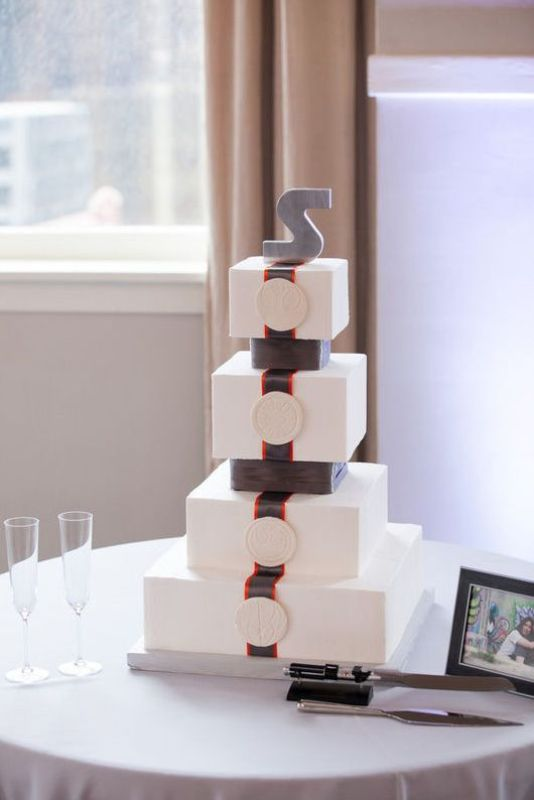 a square Star Wars themed wedding cake with a monogram on top is a lovely and cool idea