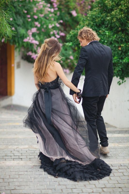 a strapless black and pink wedding dress with a lace bodice and a layered skirt with ruffles on the edge is a refined idea