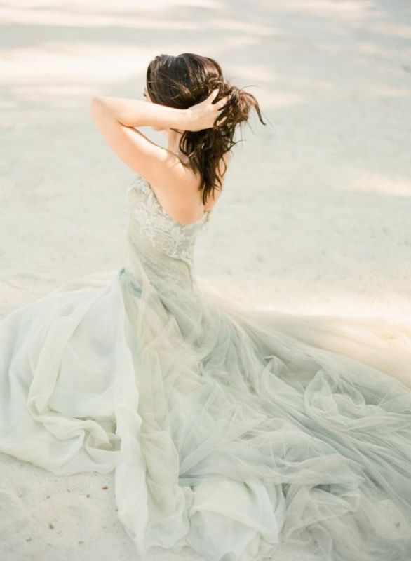 a sea foam colored A line wedding dress with a lace bodice and a layered skirt with a train for a coastal wedding