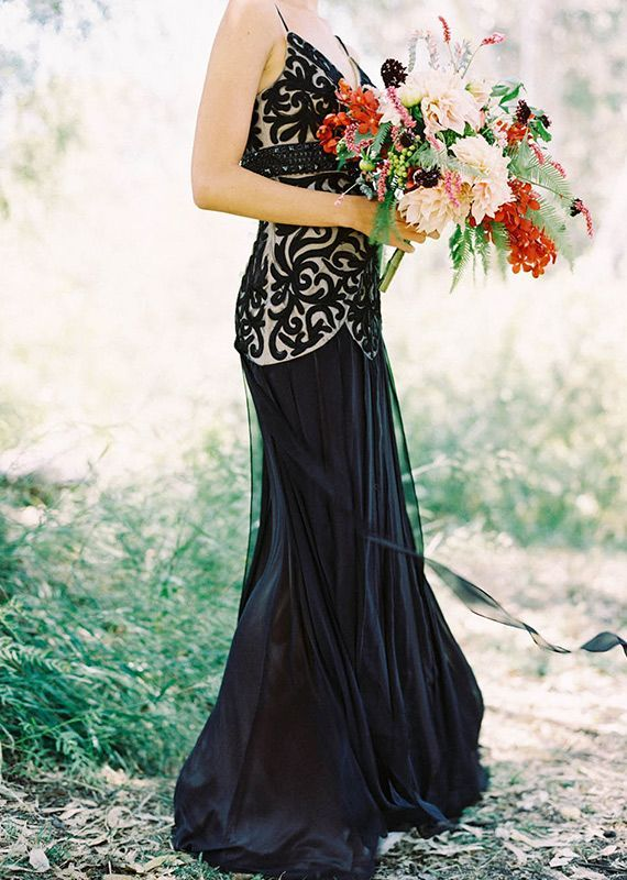a black and white spaghetti strap wedding dress with a lace embellished bodice and a pleated skirt plus a small train for a very catchy look
