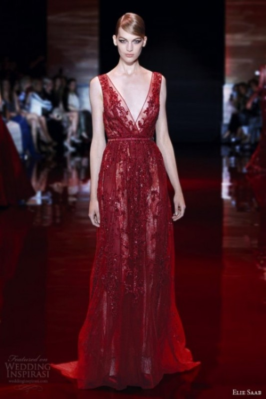 a burgundy A line thick strap wedding dress with embellishments and a train and a deep neckline is jaw dropping