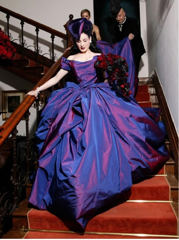 a statement purple iridescent wedding ballgown with an off the shoulder neckline and a super long train plus a hat is wow