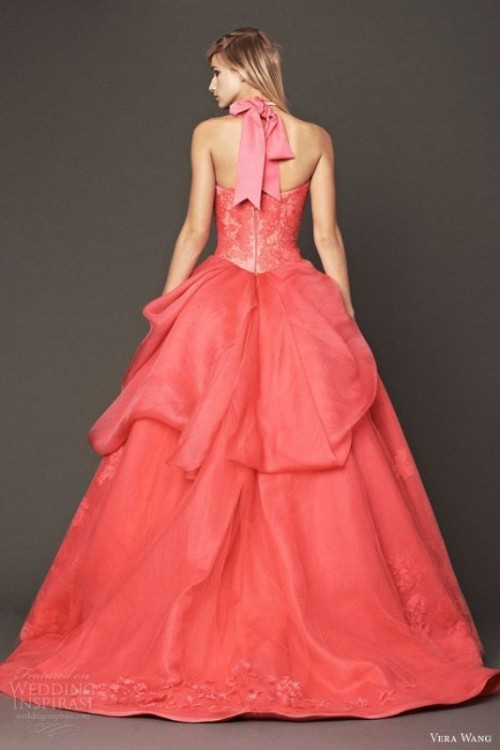 a red strapless wedding ballgown with a lace bodice and a layered skirt, a pink ribbon bow on the neck is a statement