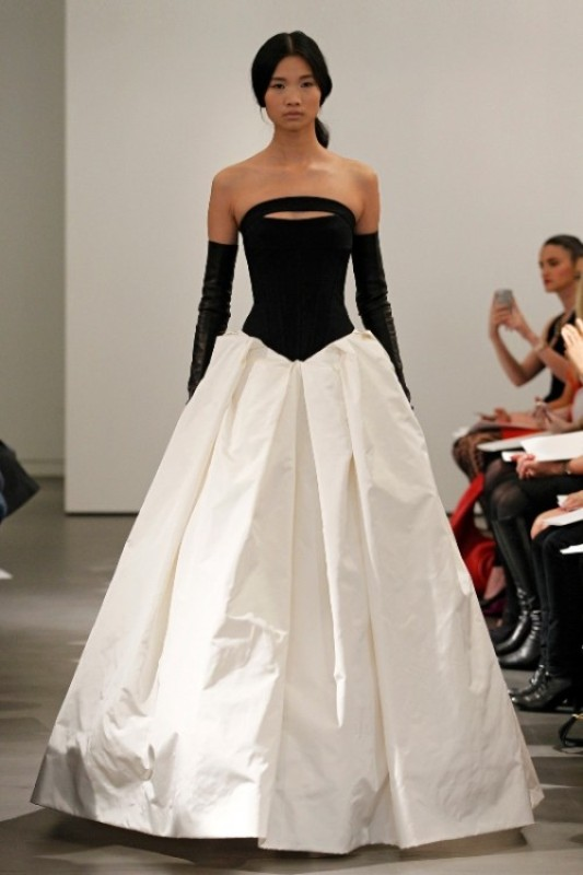 a strapless black and white wedding ballgown with a sleek bodice and a pleated skirt plus long black gloves for a statement