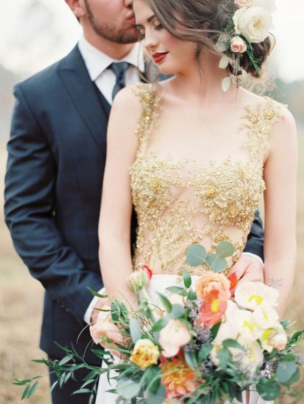 a gorgeous wedding dress with a white plain skirt and a see through bodice with strategically place gold lace appliques looks wow