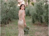 a gold sequin two piece wedding dress with a crop top with a cutout back and a cowl neckline and a mermaid skirt is a trendy and bold idea