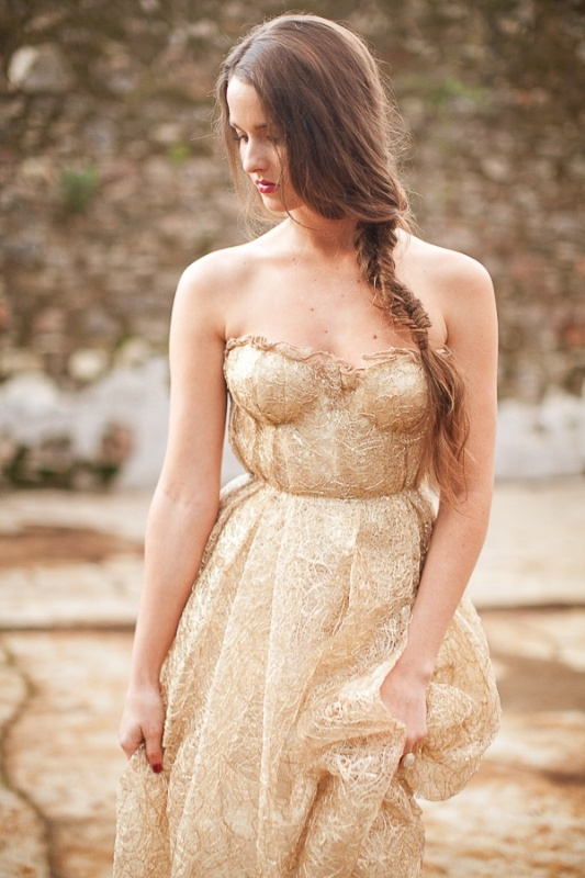 a delicate strapless gold wedding dress with a bustrier bodice and a pleated neckline plus a full pleated skirt for a romantic bride