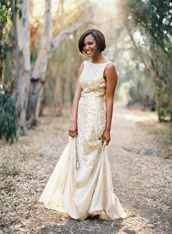 a neutral sleeveless A line wedding dress with a high neckline and shiny gold leaf appliques and a belt is very chic and bold