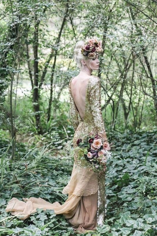 a gold sequin mermaid wedding dress with long sleeves, an open back and a tan sheer tail and train