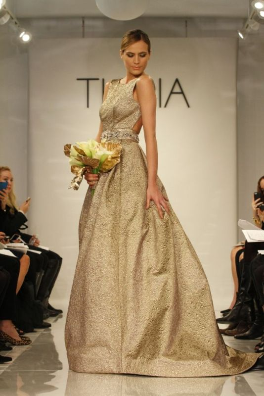 a fabulous shiny gold A line wedding dress with a sleeveless bodice, an open back and a full skirt plus a train