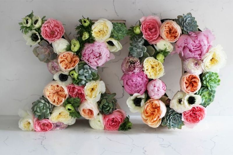 large XO flower letters done with succulents, peonies, ranunculus and some greenery look very romantic