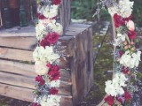 a large monogram covered with burgundy and white blooms and greenery