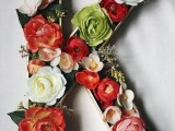 a large monogram done with red and white blooms and some greenery is a simple and stylish idea