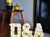 beautiful monograms with white roses are accented with lights – this will be a nice decoraiton for your reception