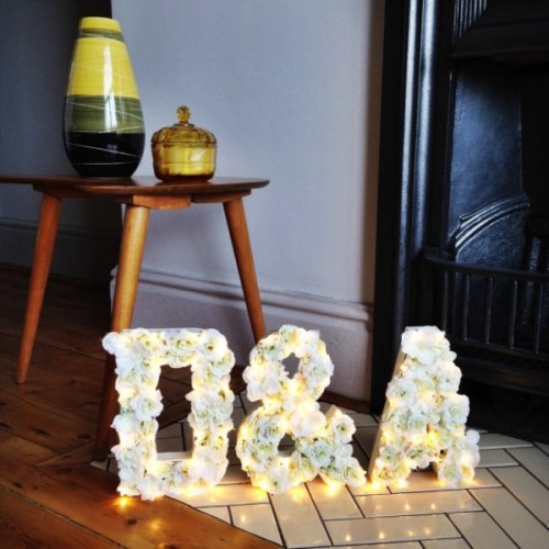 beautiful monograms with white roses are accented with lights - this will be a nice decoraiton for your reception