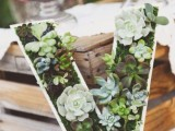 a large monogram done with moss and succulents is a very trendy idea for a wedding centerpiece