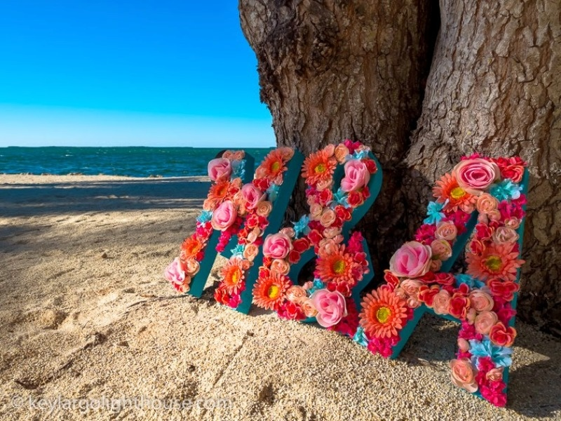 blue letters decorated with pink and fuchsia flowers are amazing for bright and colorful weddings