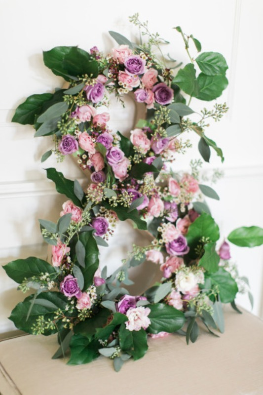 a monogram fully made of greenery and blooms is a chic wedding decoration that is non typical
