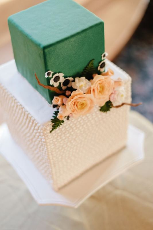 a beautiful green and white square wedding cake with a sleek and textural tier, with sugar and usual blooms and leaves is refined