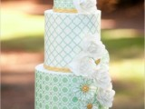 a light green and white patterned wedding cake with white and green sugar blooms for a vintage spring or summer wedding