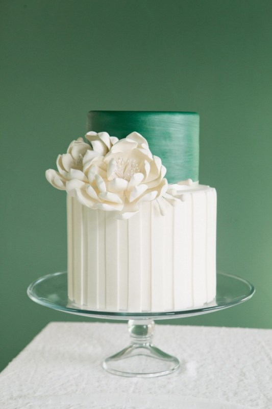 a bold round green and white wedding cake with a striped and sleek tier and some white sugar blooms for an elegant wedding