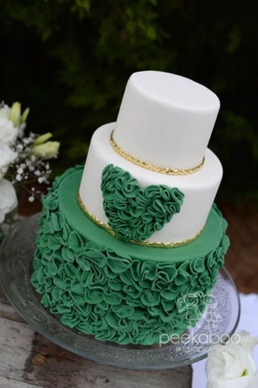 a white and emerald wedding cake with a ruffle tier and a ruffle heart plus touches of gold is refined and chic