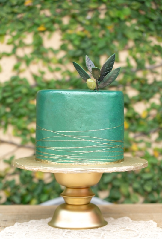 a green sleek wedding cake topped with sugar foliage and a sugar olive plus gold stripes is a gorgeous idea