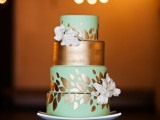 an exquisite light green and copper wedding cake with botanical patterns, a copper tier and white blooms is fantastic