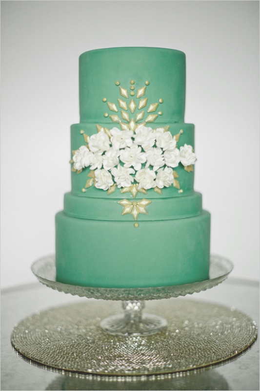 a pretty green wedding cake with white blooms, gold detailing is a very elegant and chic idea for a spring wedding