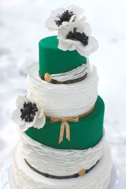 a bright emerald and white wedding cake with sleek and ruffle tiers, with white sugar blooms and leather straps for a bold summer wedding
