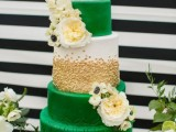 a bright emerald, white and gold wedding cake with gold polka dots, sleek and patterned tiers and white fresh blooms for a bold summer wedding