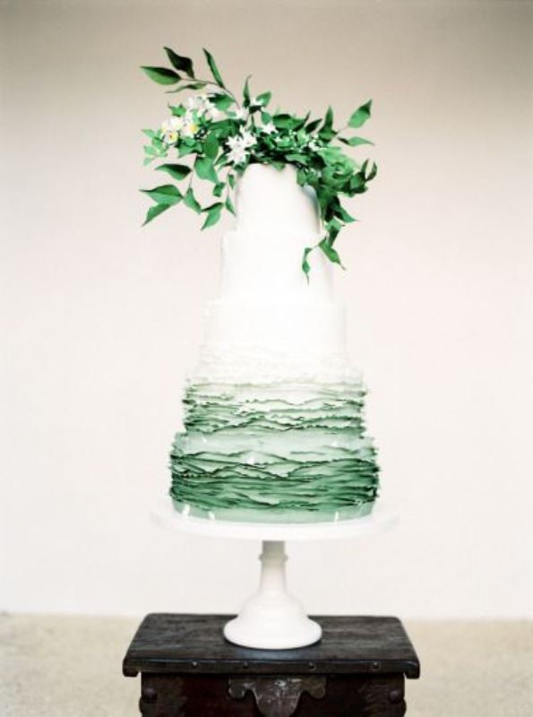 a chic wedding cake with white and ombre freen ruffle tiers, with greenery and white blooms for a spring or summer wedding