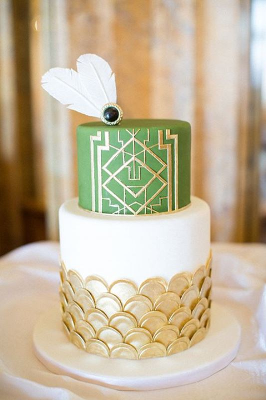 an exquisite art deco wedding cake with a green and white tier, with gold geometric detailing and gold scallops plus sugar feathers